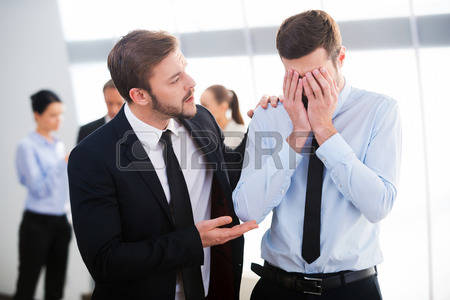 34391312-consoling-his-hopeless-colleague-young-businessman-consoling-his-depressed-colleague-with-people-sta