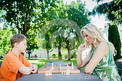 mother-son-playing-chess-park-32358815